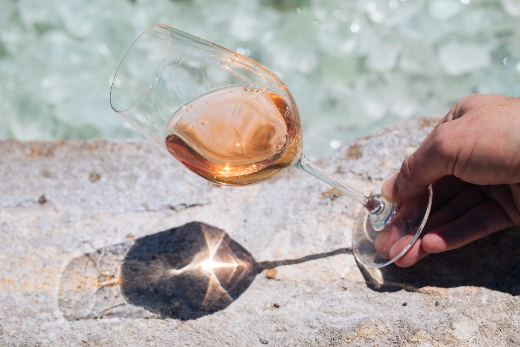 male hand holding a glass of rosé wine at an angle in front of a water feature