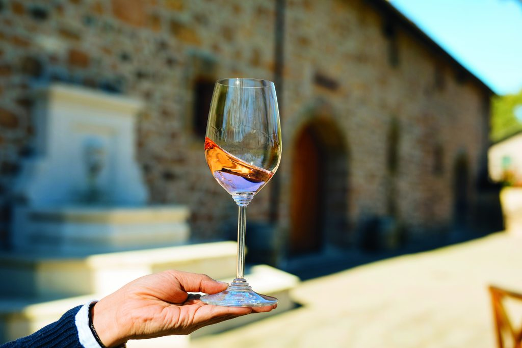 a hand holding a glass of rosé wine in front of a rock building