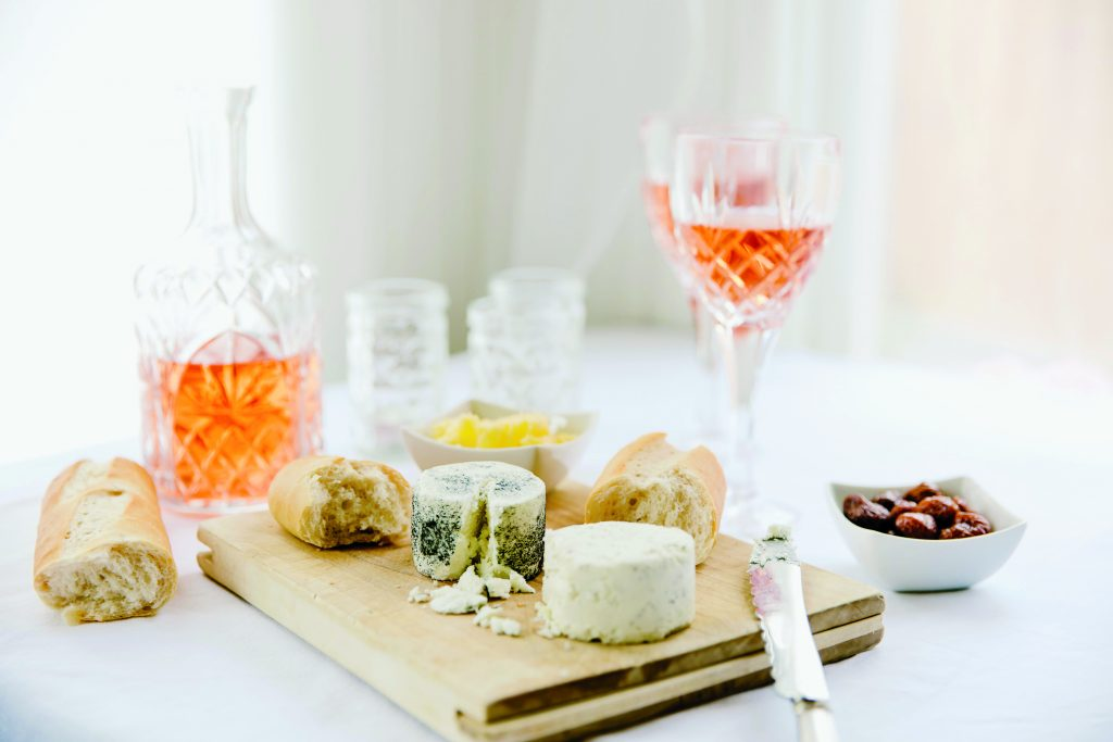 glass of rosé wine sitting on a counter with cheeses